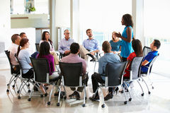 Businesswoman Addressing Multi-Cultural Office Staff Meeting. Having A Discussion Royalty Free Stock Image