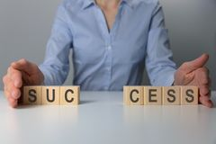 Businesswoman adjusting `success` word made of wooden blocks. Success word from wooden blocks on desk. Business success stock photography
