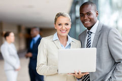 Businesswoman african businessman. Middle aged businesswoman with african businessman using laptop in office stock photo