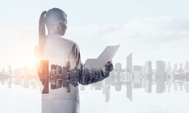 Businesswoman against modern city background . Mixed media Royalty Free Stock Photo
