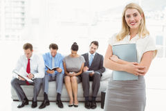 Businesswoman against people waiting for interview Stock Photos