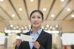 Businesswoman at the airport with airplane ticket Stock Images