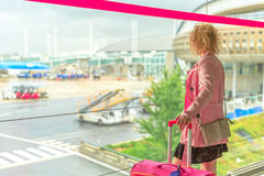 Businesswoman in airport. Looking through the window at planes. Traveler elegant caucasian woman standing with luggage watching at airport window. Blurred Royalty Free Stock Image