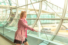 Businesswoman in airport. Looking through the window waiting for flight. Traveler elegant caucasian woman standing watching at airport window. Travel lifestyle Royalty Free Stock Photography