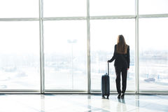 Businesswoman in airport with laggage looking at terminal panoramic windows. Businesswoman in airport looking at terminal panoramic windows Royalty Free Stock Images