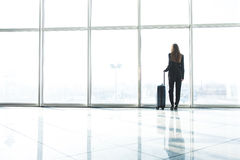Businesswoman in airport with laggage looking at terminal panoramic windows Stock Photography