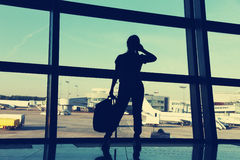 Businesswoman at the airport. Silhouette of a girl with mobile phone and backpack. business and travel Stock Photography