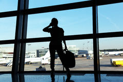 Businesswoman at the airport. Silhouette of a girl with mobile phone and backpack. business and travel Royalty Free Stock Photography
