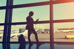 Businesswoman at the airport. Silhouette of a girl with mobile phone and backpack. business and travel Stock Photos