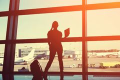 Silhouette of a businesswoman at the airport. Businesswoman at the airport. silhouette of a girl with mobile phone and backpack. business and travel Stock Images