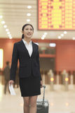 Businesswoman at the airport with suitcase and ticket Royalty Free Stock Photo