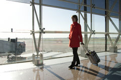 Businesswoman at airport. Traveling with trolley in red coat Stock Photography