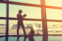 Businesswoman at the airport. Businesswoman using tablet computer at the airport. silhouette of a girl traveler with backpack. business and travel Stock Images