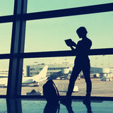 Businesswoman at the airport. Businesswoman using tablet computer at the airport. silhouette of a girl traveler with backpack. business and travel Royalty Free Stock Image