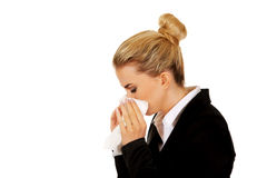 Businesswoman with an allergy sneezing into tissue Stock Photography