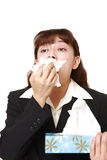 Businesswoman with an allergy sneezing into tissue Royalty Free Stock Images