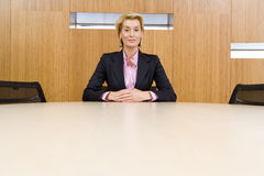 Businesswoman alone at conference table, hands clasped, portrait, low angle view stock photos