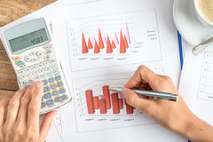 Businesswoman analysing statistical graphs. Using a manual calculator, view from above of her hands and paperwork on a wooden desk Royalty Free Stock Photos