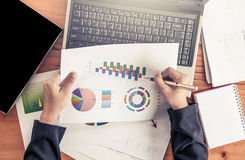 Businesswoman analyzing business report with charts and graph Royalty Free Stock Image