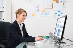 Businesswoman analyzing graph on computer Stock Photo