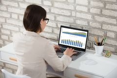 Businesswoman Analyzing Graph On Laptop Stock Images