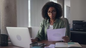 Businesswoman analyzing the graph and typing on laptop. Close-up of a young african businesswoman analyzing the graph and typing on laptop in modern office stock video