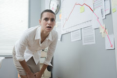 Businesswoman analyzing negative business chart. Stunned businesswoman checking a financial business chart on office wall with arrow going down Stock Photography