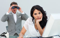 Businesswoman annoyed by a man using binocula Stock Photos
