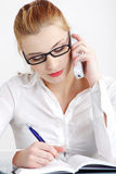 Businesswoman answering the phone and writing. Royalty Free Stock Photography