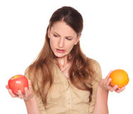 Businesswoman - apple and orange choice. Isolated studio shot of a Caucasian businesswoman comparing an apple to an orange and trying to make a decision Stock Images