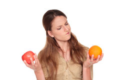 Businesswoman - apple vs orange. Isolated studio shot of a Caucasian businesswoman making a difficult choice between an apple and orange Royalty Free Stock Images