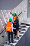 Businesswoman and architects standing on a staircase discussing with blueprint Stock Photography