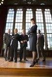Businesswoman with arms crossed by businessmen in hall, portrait, low angle view Stock Images