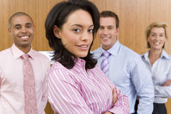 Businesswoman with arms crossed by colleagues, smiling, portrait, close-up royalty free stock photography