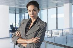 Businesswoman With Arms Crossed In Office Corridor Royalty Free Stock Photos