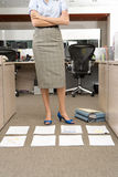 Businesswoman with arms crossed by piles of paperwork on floor in office, low section Stock Photography
