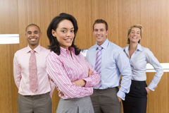 Businesswoman with arms crossed, smiling, portrait, colleagues in background Royalty Free Stock Photos