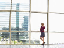 Businesswoman With Arms Crossed Standing By Window Stock Photo
