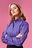 Businesswoman with arms folded. Wearing striped shirt on a pink background Royalty Free Stock Image