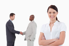 Businesswoman with arms folded and hand shaking trading partners Stock Photography