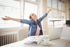 Businesswoman with arms outstretched while sitting at office Stock Image