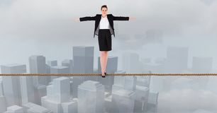Businesswoman with arms outstretched standing on rope over city. Digital composite of Businesswoman with arms outstretched standing on rope over city stock illustration