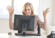 Businesswoman With Arms Raised Celebrating Success While Looking. Happy young businesswoman with arms raised celebrating success while looking at computer in royalty free stock photography