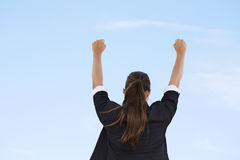 Businesswoman with arms up against blue sky. Rear view Royalty Free Stock Image