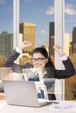 Businesswoman with arms up and a laptop Stock Photo