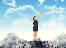Businesswoman with arms up on mountain top Stock Photography
