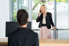 Businesswoman arrive to hotel check in talking on phone. Businesswoman arrive to hotel check in talking on the phone Stock Photography