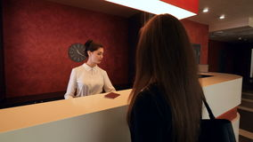 Businesswoman arrives to the hotel at the reception and get a key. 4K.