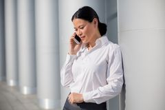 Businesswoman. Asian young businesswoman using cell phone near office buiding. Woman in white shirt speaking with her partners Royalty Free Stock Photos