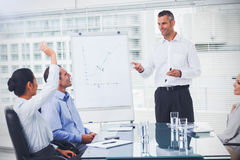 Businesswoman asking question during her colleagues presentation. In bright office Stock Photography